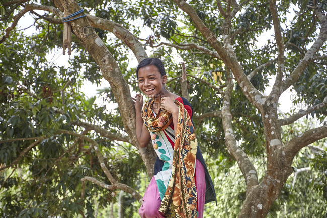 Nirala Para village, Bangladesh - May 1, 2013: A happy young Khasi tribe girl climbing a tree
