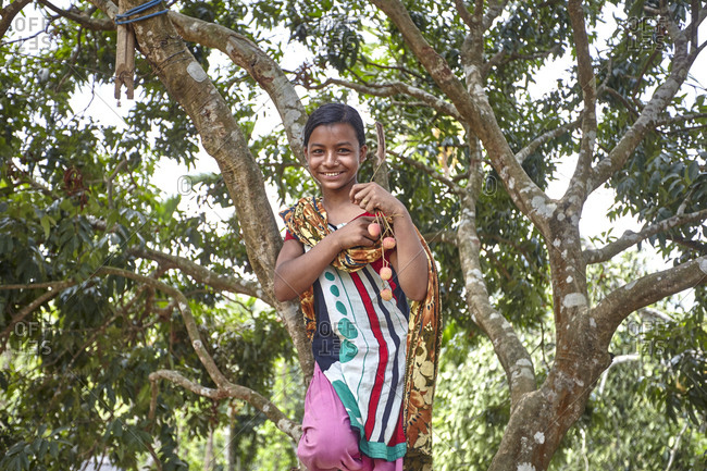 Nirala Para village, Bangladesh - May 1, 2013: Portrait of a happy young Khasi tribe girl climbing a tree