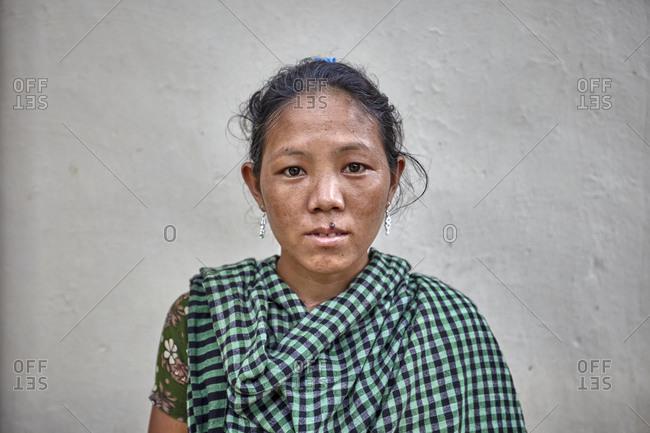 Nirala Para village, Bangladesh - May 2, 2013: Portrait of a Khasi woman in front of a white wall