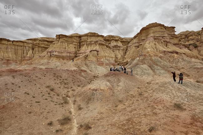 Gobi Desert, Mongolia - July 13, 2015: Tourists viewing the Tsagaan Suvarga cliff in the Gobi Desert