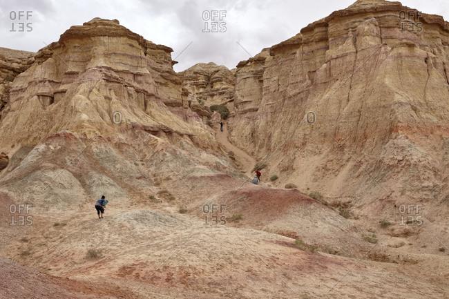 Gobi Desert, Mongolia - July 13, 2015: Tourists exploring the Tsagaan Suvarga cliff in the Gobi Desert