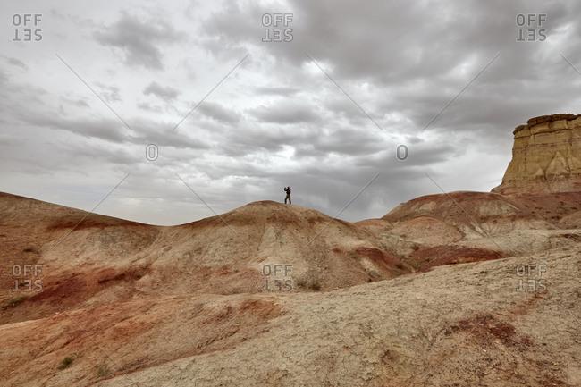 Man taking picture from cliff at Tsagaan Suvarga (White Stupa) in the Gobi Desert, Mongolia