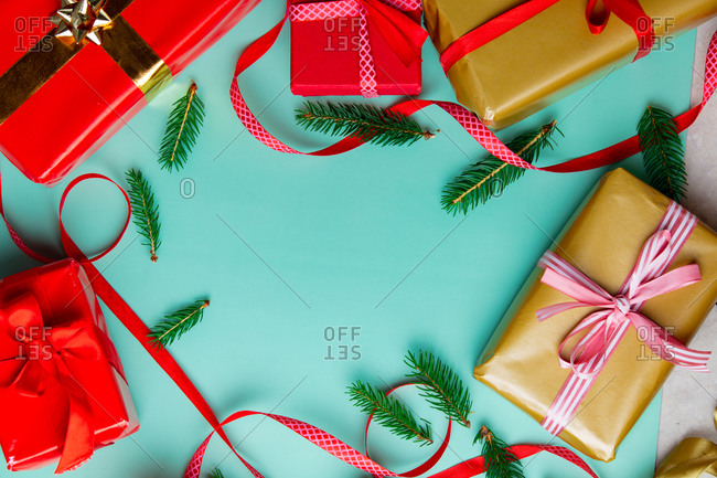 Christmas gifts with ribbons and pine tree branches on blue background