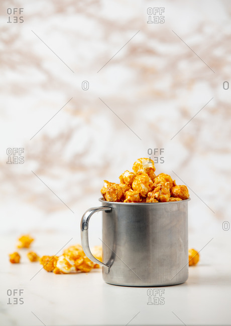 Sweet popcorn in caramel in a mug on the table