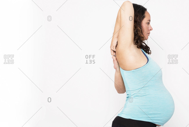 Young pregnant woman practicing yoga in front of white background