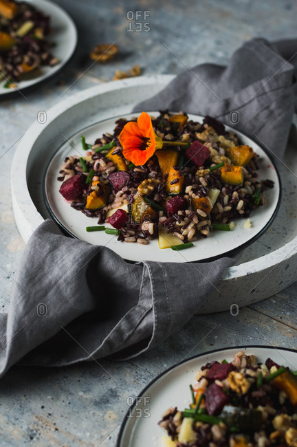 Brown and black rice salad with roasted beetroot, pumpkin and chives with edible flower