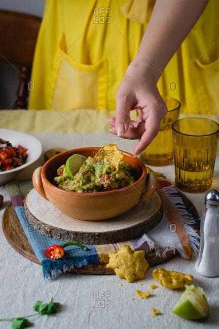 A woman reaching for tortilla chip in guacamole dip
