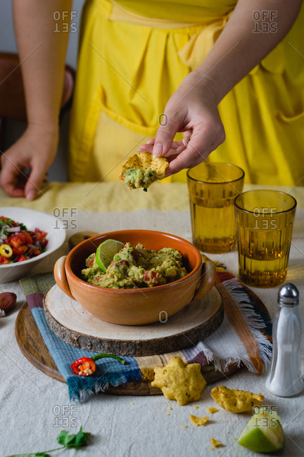 A woman taking guacamole with corn tortilla chips
