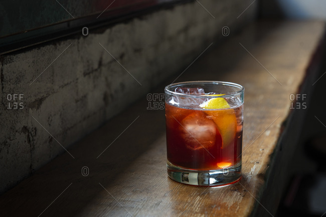 Red cocktail on the rocks on a rustic wooden bar
