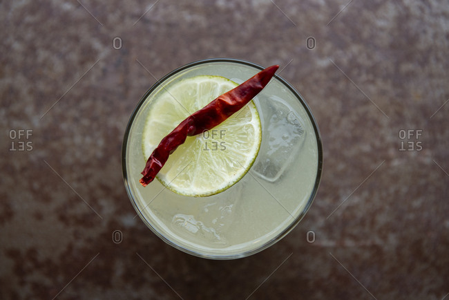 Margarita on the rocks with a chili and lemon garnish from above