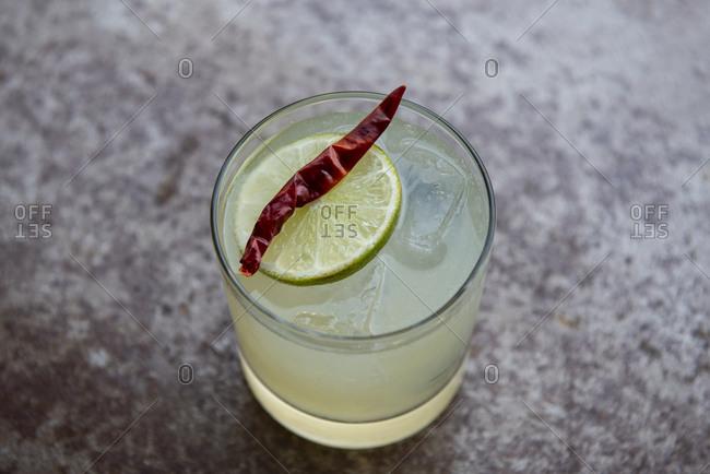 Margarita on the rocks with a chili and lemon garnish