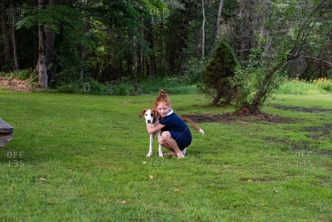 Young girl hugs dog on a lawn