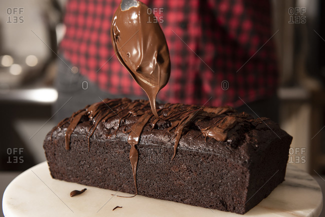 Close up of a baker icing a chocolate loaf cake