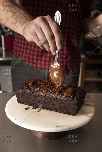 Baker icing a chocolate loaf cake