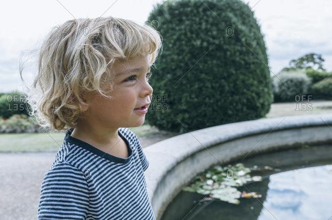 Portrait of tan blonde kid outside by a fountain