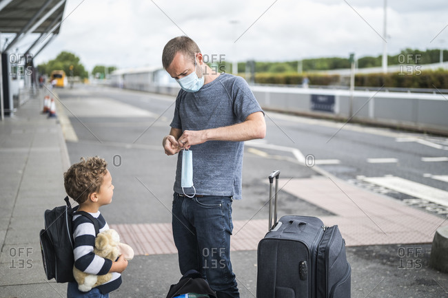 Father at drop off in airport holding mask for his son
