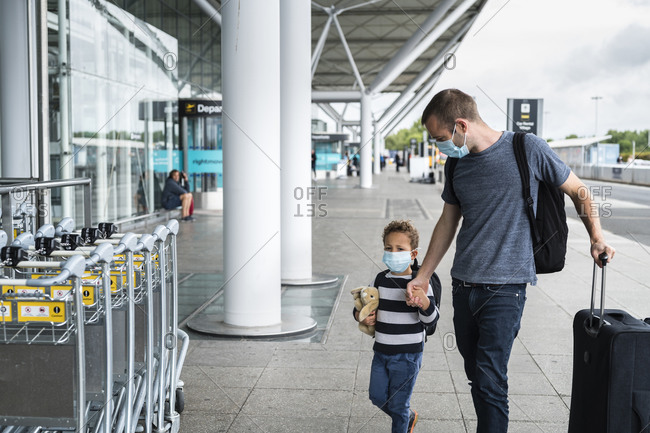 Father and son arriving at airport wearing masks during pandemic