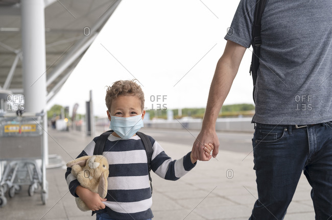 Child walks in airport wearing mask during pandemic
