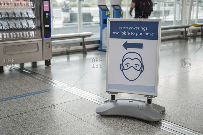 Sign that shows face coverings are available for purchase at airport.