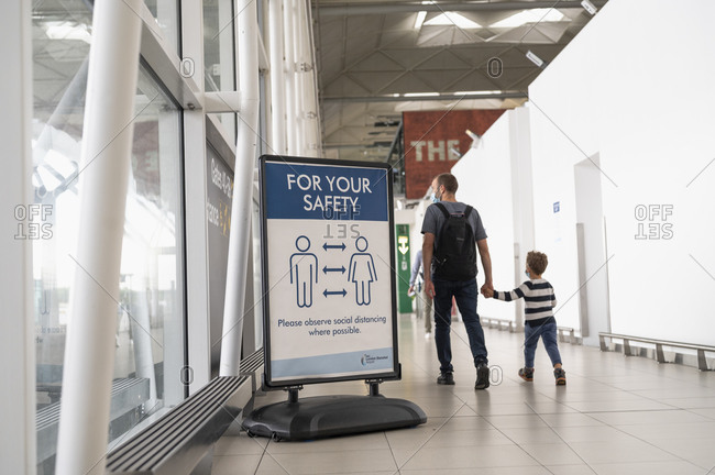 London, United Kingdom - July 08, 2020:  Father and son walking by a social distancing warning at London Standsted airport.