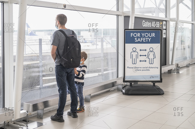London, United Kingdom - July 08, 2020:  Father and son standing by a social distancing warning at London Standsted airport.