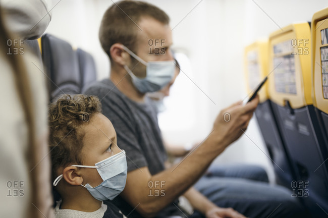 Father and son waiting for flight departure in airplane wearing masks