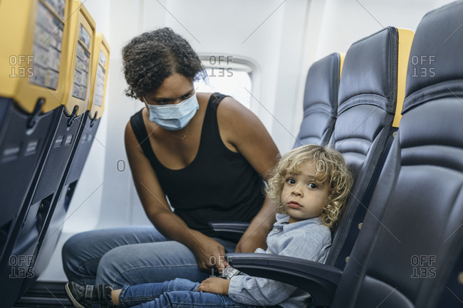 Mother wearing masks during pandemic attached son before flight departure