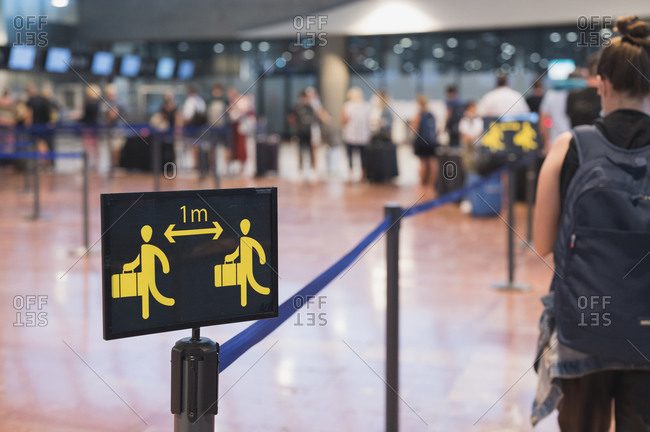 People queuing next to social distancing sign in airport