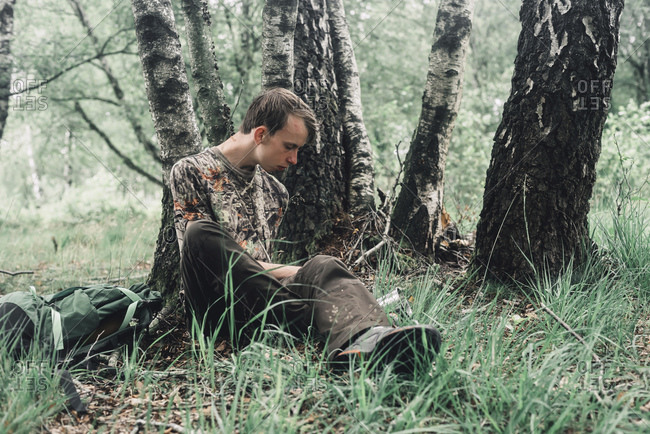Young man sitting in grass by birch trees