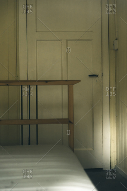 Dilapidated bedroom with white wooden door
