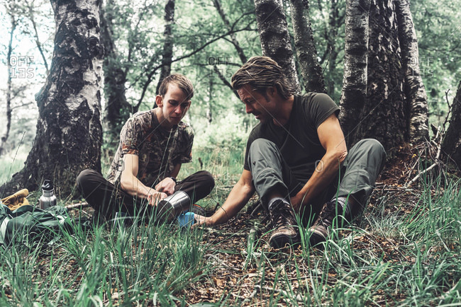 Two men enjoying coffee while sitting in grass in forest