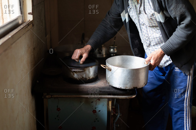 Misiones, Argentina - February 6, 2015: Man preparing tea in a traditional rural kitchen from with kettle and pots
