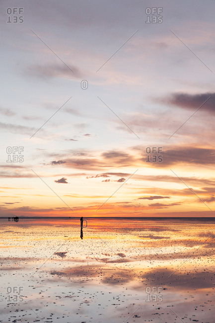 Idyllic sunset view of a man in Salt lake in Uyuni, Bolivia, South America