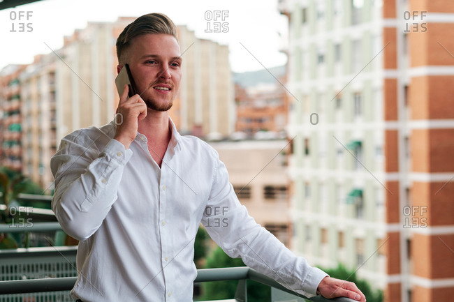 Young executive using his mobile phone on the balcony with a city background