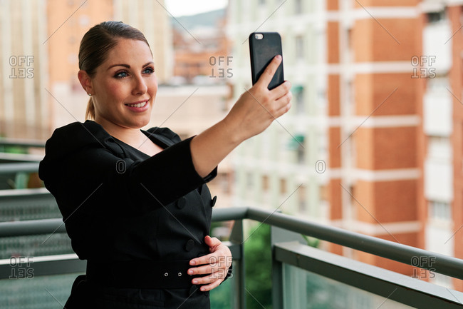 Young woman executive using a mobile phone on her balcony with city background