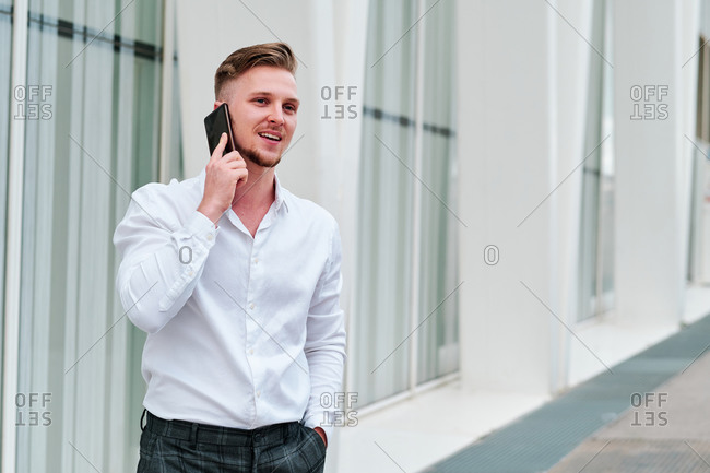Young executive using his mobile phone outside of his office