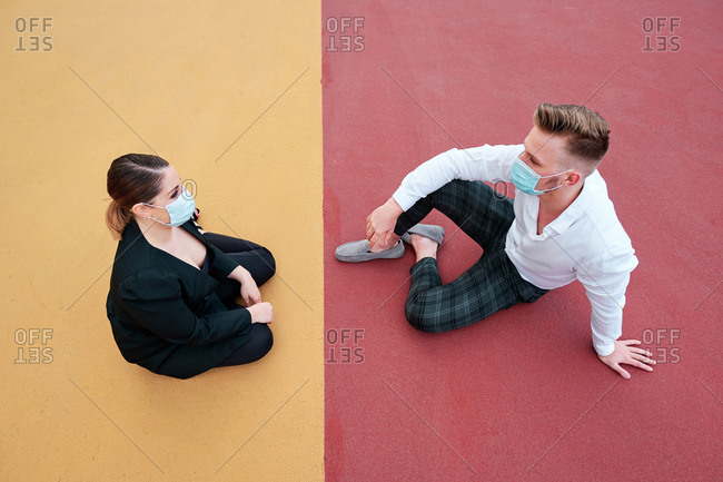 A young man and woman with face masks sitting on the ground and talking