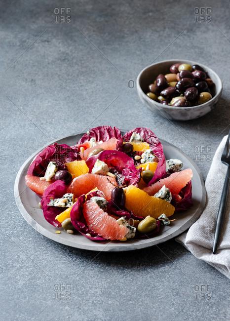 Radicchio salad with citrus on gray rustic plate