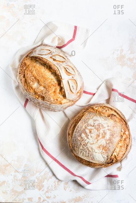 Loaves of freshly baked homemade sourdough bread on light background