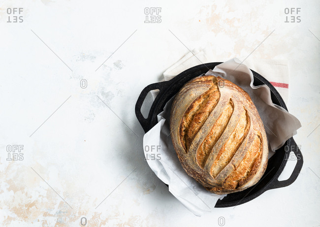 Loaf of freshly baked homemade sourdough bread in cast iron pan
