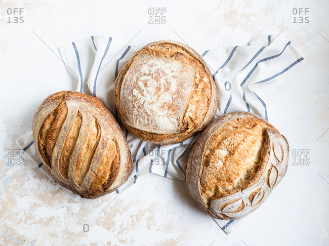 Three loaves of freshly baked homemade sourdough bread, top view