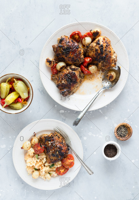 Roasted chicken thighs with pearl onions and tomatoes served with mashed potatoes and pickled peppers