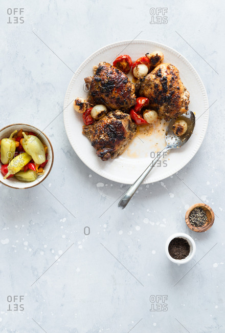 Roasted chicken thighs with pearl onions and tomatoes served with pickled peppers