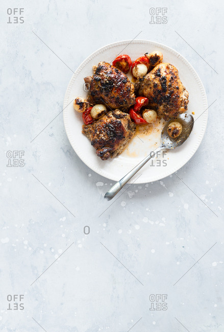 Roasted chicken thighs with pearl onions and tomatoes on a plate, top view