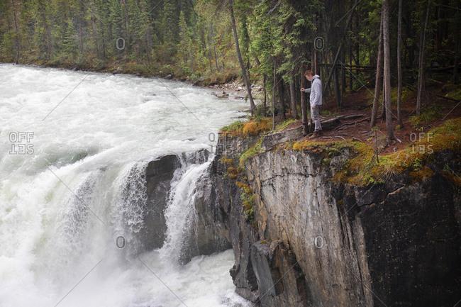 Young man dangerously close to river edge at Sunwapta Falls in the Canadian Rockies, Jasper National Park, Canada