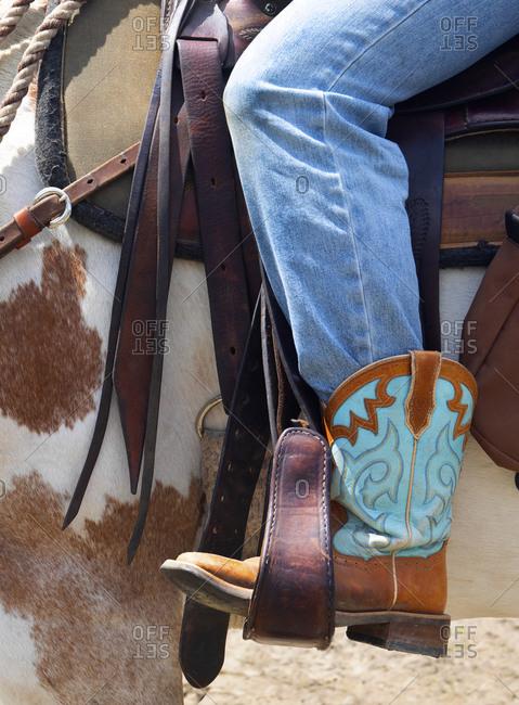 Female horse rider wearing cowboy boots, Merritt, British Columbia, Canada