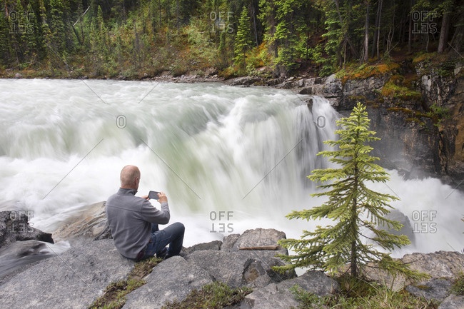 Tourist taking photograph with smart phone of Sunwapta Falls in the Canadian Rockies