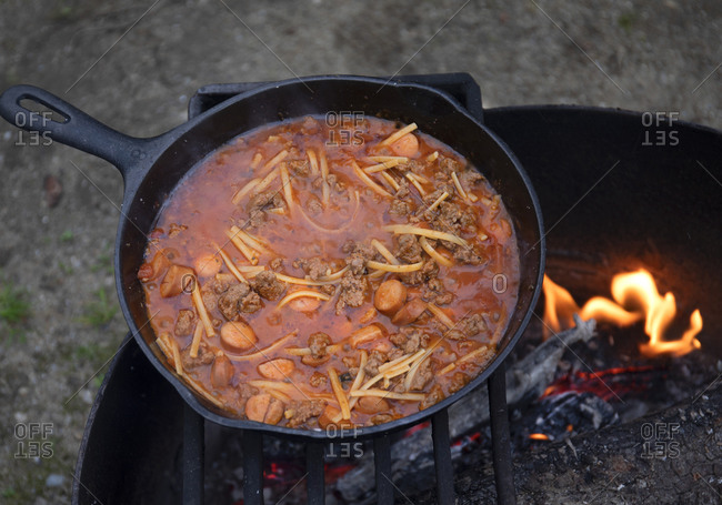 Cooking stew for dinner over a campfire, British Columbia, Canada