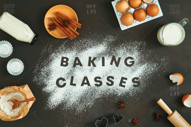 Baking class written in white flour on table, surrounded by baking tools.