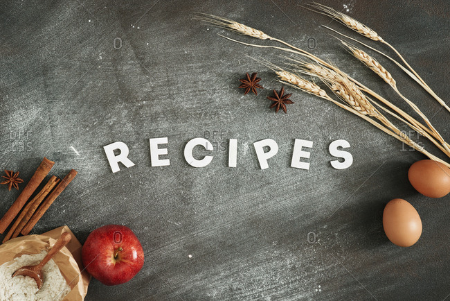 Recipes poster design with cake ingredients on black chalkboard from above.